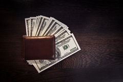 Money in leather wallet. Money in a leather wallet on a dark wooden desk Stock Photo