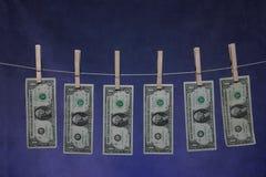 Money Line. Money hanging on line. 6 US dollar bills. Money Laundering metaphor Stock Photos