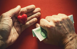 Money or Love. Conceptual composition about love or money, two male hands, one holds money tightly and other red heart as symbol of love Royalty Free Stock Photography