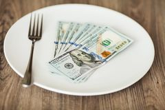 Money lying on the plate with fork. Dollars photo. Greedy corruption concept. Bribe idea.  stock image