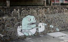 Money machine. Street art in Vienna showing a creature with a money machine Stock Photos