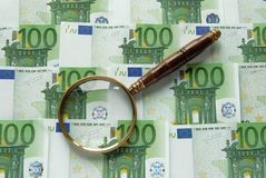 Money and Magnifier Stock Photo