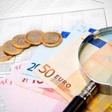 Money and magnifier for documents. Stock Photo