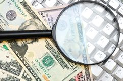 Money and magnifier for the keyboard. Stock Photos