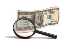 Money and magnifying glass Stock Image