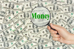 Money and magnifying glass in hand Royalty Free Stock Photography