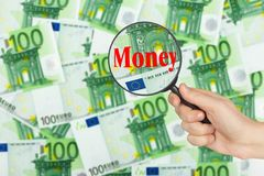 Money and magnifying glass in hand Royalty Free Stock Images