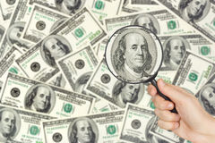 Money and magnifying glass in hand Stock Photos
