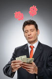 Money-maker. Funny businessman with a dollar hornes on the head Stock Photo