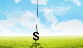 Money making concept. Mixed media. Dollar sign hanging on rope from cloud. Mixed media stock photos