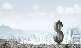Money making and wealth concept presented by stone dollar symbol on natural landscape Stock Photo