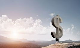 Money making and wealth concept presented by stone dollar symbol on natural landscape Stock Photography