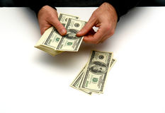 Money man. Man counting out hunderd dollar bills in three stacks on white table Royalty Free Stock Photo