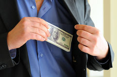 Money. Man in a putting money in his pocket Stock Images