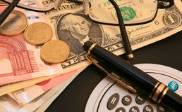 Money Management. Calculater pen.glasses,bank notes with small change Stock Photography