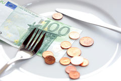 Money management. One hundred Euros bill and cents on a white plate, with fork and knife -- concept money management, budgeting, financial security, rising cost Stock Photos