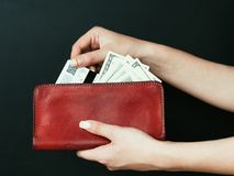 Money management shopping spending cash wallet. Money management. personal finances and income. shopping and spending cash. woman hands holding a red leather royalty free stock image