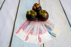 Money with mangosteen fruit Royalty Free Stock Photo