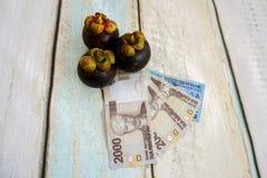 Money with mangosteen fruit. Indonesian rupiahs with mangosteen fruit Royalty Free Stock Photography