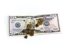 Money and marijuana. A 50 dollar US currency bill with marijuana pot buds on top, over white Stock Photography