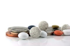 Money or medicine 2 ??. Close up of a pills and money on a white reflective background Royalty Free Stock Photo