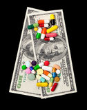 Money for Medicine. Two 100 dollar bills covered with some pills and capsules Stock Photo