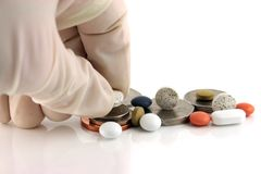 Money or medicine 3 ??. Hand in a surgical glove going for the pills not the money Stock Photo