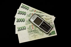 Money with mobile phone. Czech banknotes with mobile phone on black background Stock Images