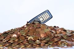 Money and mobile phone. Cell phone diving in pile of euro coins, Sharp in the middle of the pile Stock Photography