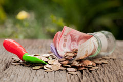 Money and money jar with shovel and cash, Saving money concept, Royalty Free Stock Image