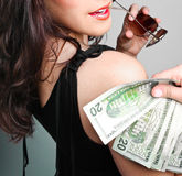 Money Money Money. Photograph of a young woman holding money bills over her right shoulder Stock Photos