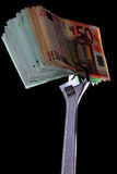 Money and monkey-wrench. Stack of money caught in silver monkey-wrench stock image