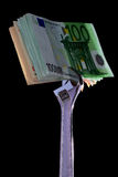 Money and monkey-wrench. Stack of money caught in silver monkey-wrench stock photography