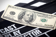 Money on a movie clapper royalty free stock photography