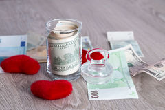Money near red hearts. Dollars in open jar with euro on grey wooden background.  Copy space. Love. Valentine day. Stock Photos