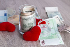 Money near red hearts. Dollars in open jar with euro on grey wooden background.  Copy space. Love. Valentine day. Money near red hearts. Dollars in open jar Royalty Free Stock Images