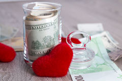 Money near red hearts. Dollars in open jar with euro on grey wooden background.  Copy space. Love. Valentine day. Money and red hearts. Dollars in open jar on Stock Images