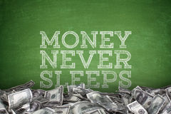 Money never sleeps on blackboard background Royalty Free Stock Photo