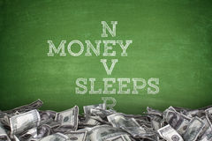 Money never sleeps on blackboard background Royalty Free Stock Image