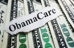 Money and Obama Care. Closeup of an Obamacare newspaper headline on cash Stock Photo