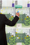 Money obsession. Businessman is painting a money wall royalty free stock photography