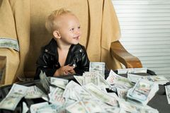 Money obsession. Little boy count money in cash. Small child do business accounting in startup company. Startup business. Costs. Little entrepreneur work in stock photography
