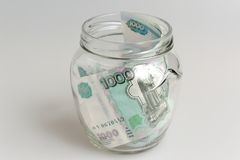 Money in open glass jar on gray background Stock Photo
