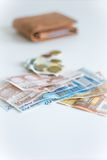 Money out of wallet. Stack of Euros with some change with a leather wallet on the background royalty free stock photos
