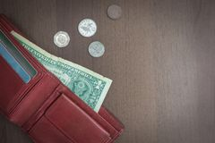 The money is over. From the purse sticks out one dollar, next to small coins. Lack of money, low salary. Muted tone, vignetting royalty free stock image