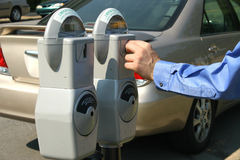 Money in Parking Meter. Adult male hand putting money in a parking meter.  Shot with a Canon 20D Stock Photo
