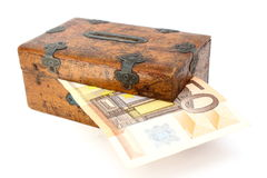 Money partly in wooden box. Over white background Royalty Free Stock Photography