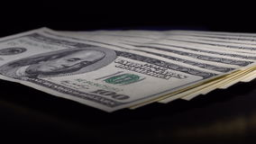 Money and passport on the table. Denominations dollars in the passport are rotated on the black desk stock video