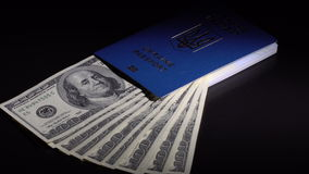 Money and passport on the table. Denominations dollars in the passport are rotated on the black desk stock footage