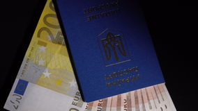 Money and passport on the table. Euro banknote in the passport are rotated on the black desk stock footage